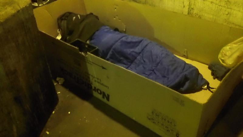 Homeless Person living in a cardboard box under lower wacker in city of Chicago,